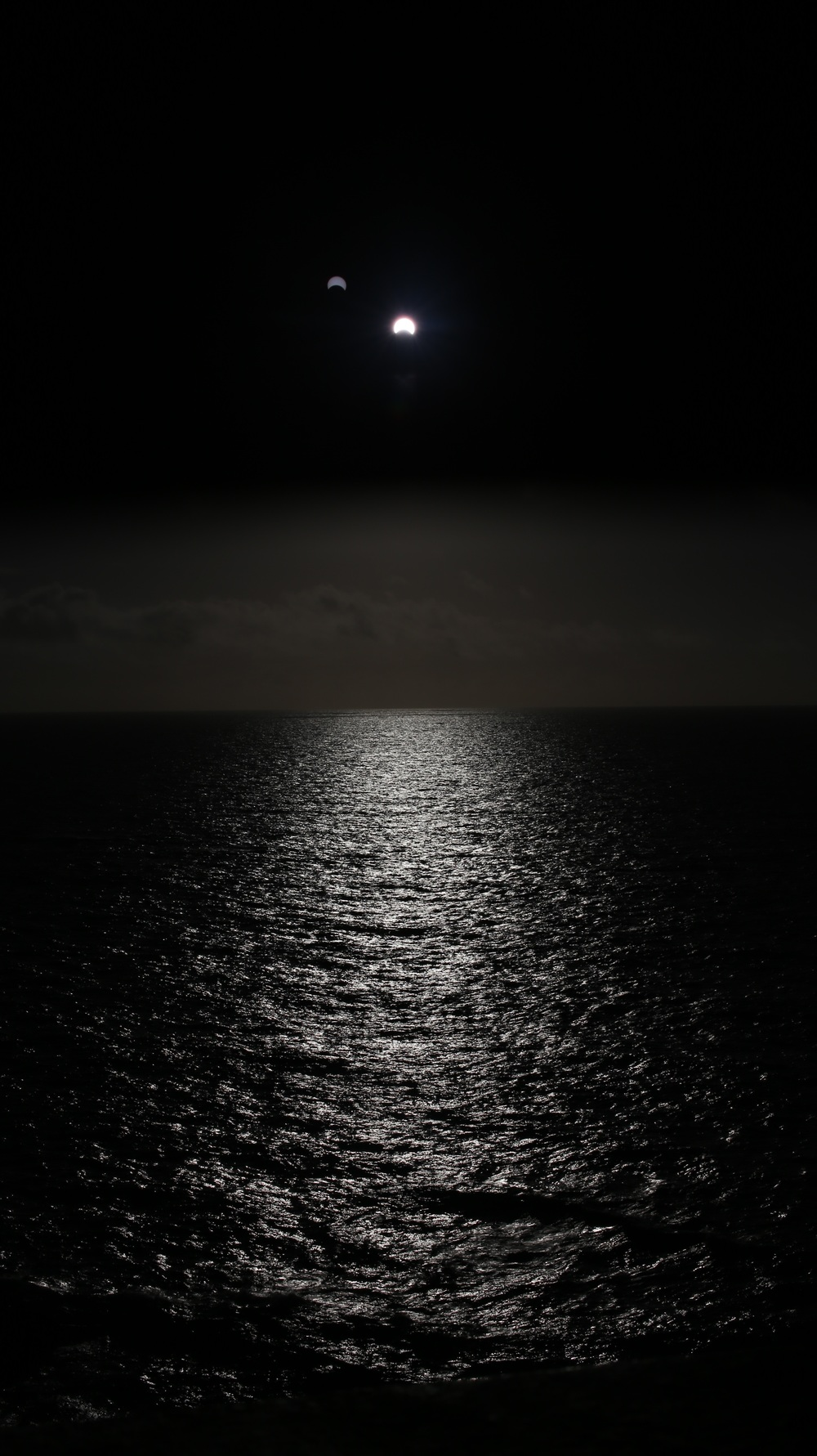 While Xavier Jupier was flying directly into the middle of the Bermuda Triangle where he captured his remarkable image of the Hybrid Eclipse (seen above) , Leslie Kothmann and Mark Bender were on the island of Bermuda in hope of witnessing a 97% partial phase at sunrise rising out of the sea. The expectation and hope was that at 97% we would see something akin to the annularity seen in Western Australia (seen above). This was not be, as while the previous three days had seen clear skies on the horizon, the day of the eclipse saw thick cloud cover that completely obscured the eclipse. It was many minutes later before we could see the sun burst out above the clouds and by the time I imagined the above composition, we were only seeing about 40% occultation.