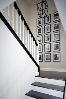 Traditional stairway landing by J Hill Interiors (Coronado) with an installation of black-and-white images.