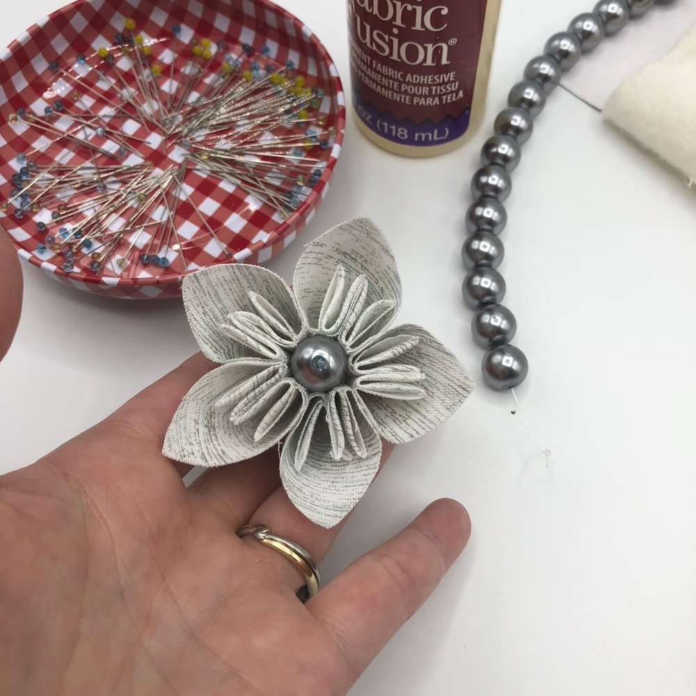 Completing the Flower - Wad up a scrap of batting, dab with glue, and insert into the flower. Use a glass head pin to secure a bead in the middle of the flower.
