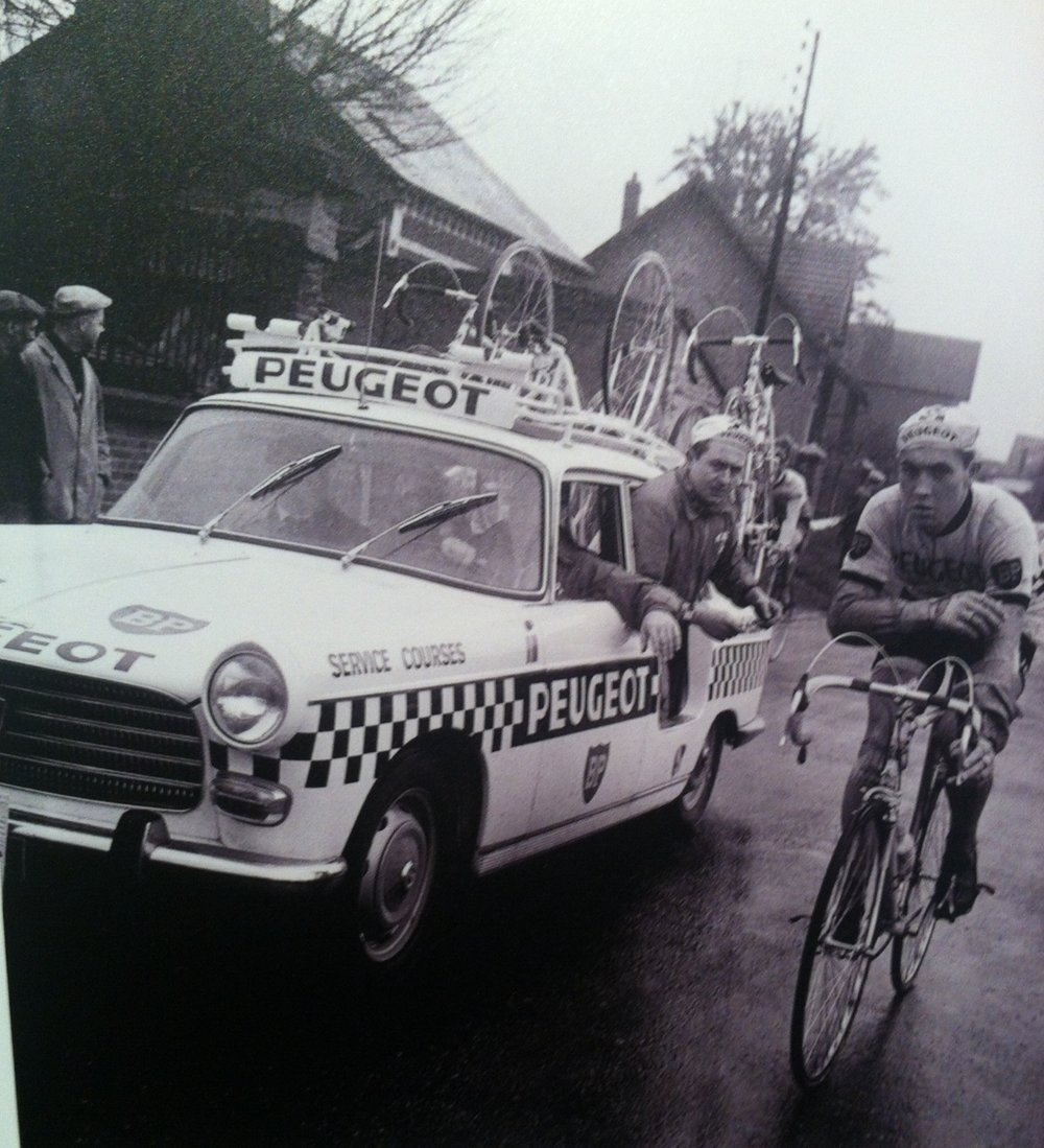 Eddy Merckx in the 1967 Paris Nice beside the Peugeot 404 team car. The picture highlights the mechanic sitting through the back rear door flap (no window no door panel). Peugeot team cars had a different decal placement at the Tour de France.