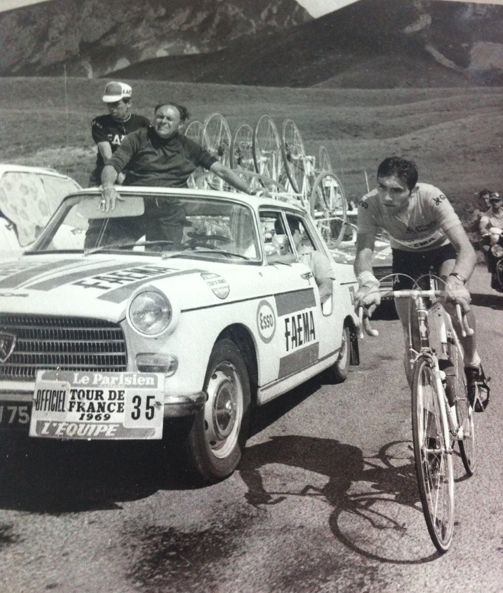 Eddy Merckx at the 1969 Tour de France. Note the mechanic's rear door & a somewhat regal Lomme Driessens hanging out the roof.