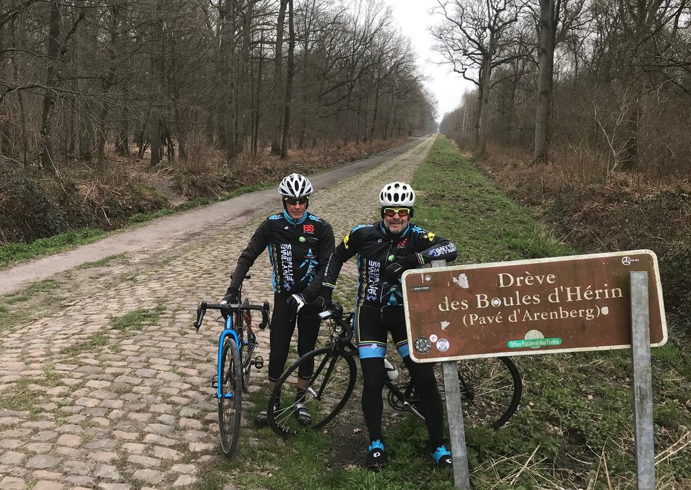 """Roubaix Recon Ride @ 28 Mar  - Mike Lawson & Marty Wright at the Arenberg Forest cobbles   Roubaix Recon Ride Report @ 28 Mar   Barely an hour's drive from the Kokerelle B&B in Oudenaarde, down through Tournai and across the Belgian-French border at Saint-Amand les-Eaux to the Arenberg Forest cobbles. Marty Wright neatly summed it up … """"Well, the Arenberg Forest cobbles, that was total bullshit ! !"""" …  The next cobbled sector came almost immediately at Wallers for the Gibus Pont (Sector 18). Somehow the lads completely missed Sector 17 (not sure how that happened), but cobbled hostilities were quickly resumed at both Warlaing & Brillon (Sectors 16 & 15). Both were hard & uncomfortable. Again we somehow inadvertently missed Sector 14 (what happened there ?) and leapfrogged straight onto Orchies at Sector 13. After Orchies the bikes were packed into the truck & we headed straight for the Roubaix Velodrome and a chance for Marty to do a few free laps around an iconic velodrome."""