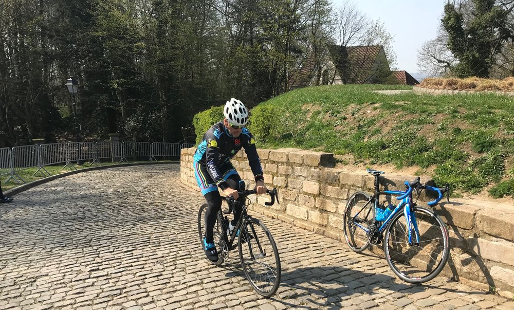 Muur (Wall) of Geraadsbergen @ 1 April  - Marty Wright climbs the Kapel Muur (Chapel Wall) cobbles   Muur Ride Report @ 1 April   A 70k ride was on the menu with small Flemish back lanes towards Brakel, where we joined the official Tour of Flanders race route and simply followed the race route signs already posted for next weekends Flanders Classic. Then it was through Brakel and on towards the cobbled Muur of Geraadsbergen. As cobbled climbs go the Muur maybe is the most famous but is neither the steepest nor the most difficult (Patersberg is much more uncomfortable) and everybody got to the Muur summit comfortably.