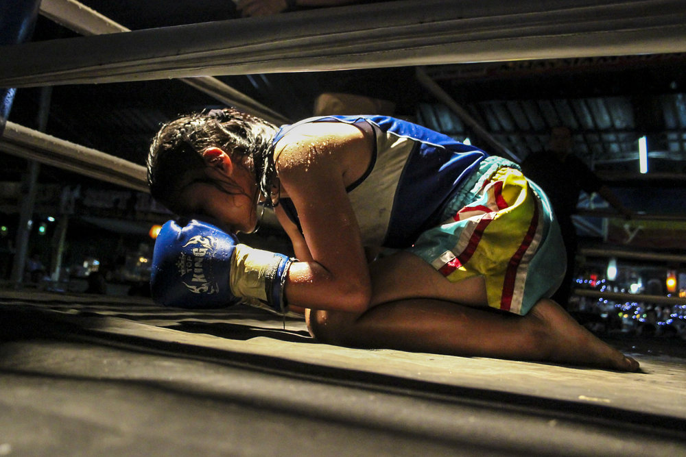 Muay Thai is more than just boxing in Thailand, it is a sport laden with sacred rituals and traditions. Before her fight, the teenage girl bows to the corner of each ring as part of 'wai kru ram muay'.