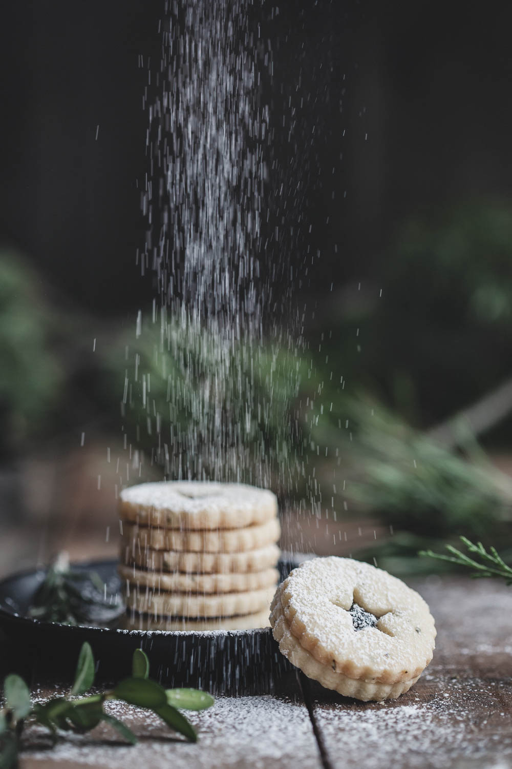 A dusting of powdered sugar completes the rosemary shortbread Linzer cookies with blueberry jam