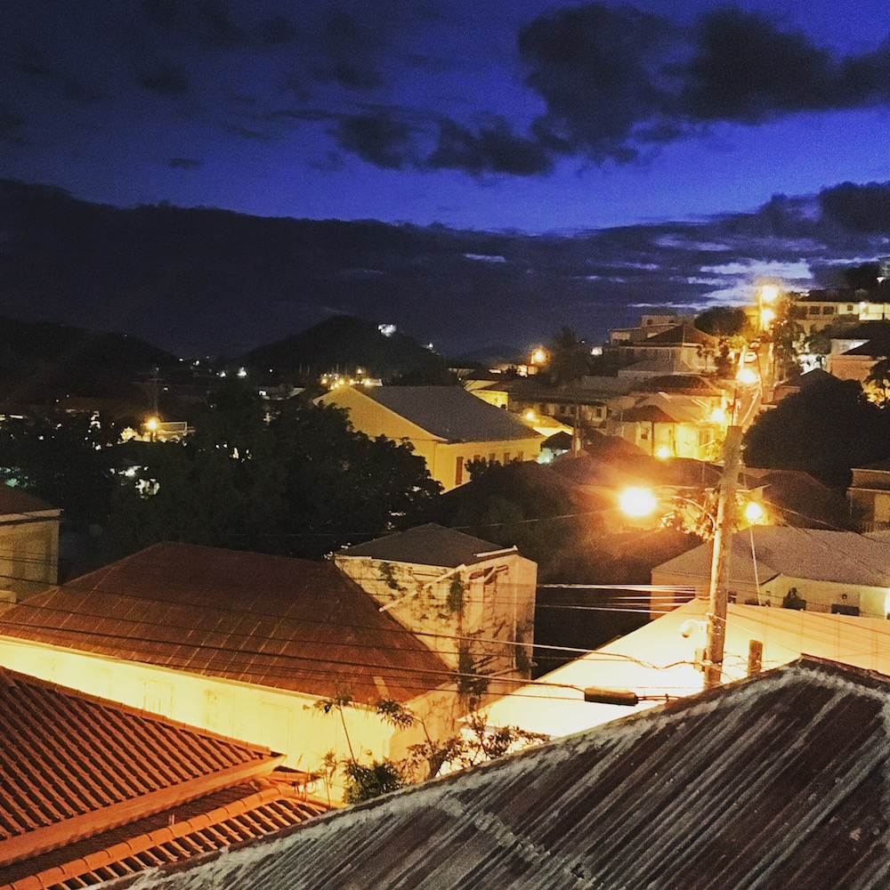 The Sugarcane Grille overlooks a courtyard with a small pool in one direction, and this charming cityscape where dusk hangs beautifully in the sky as street lambs climb the hill.