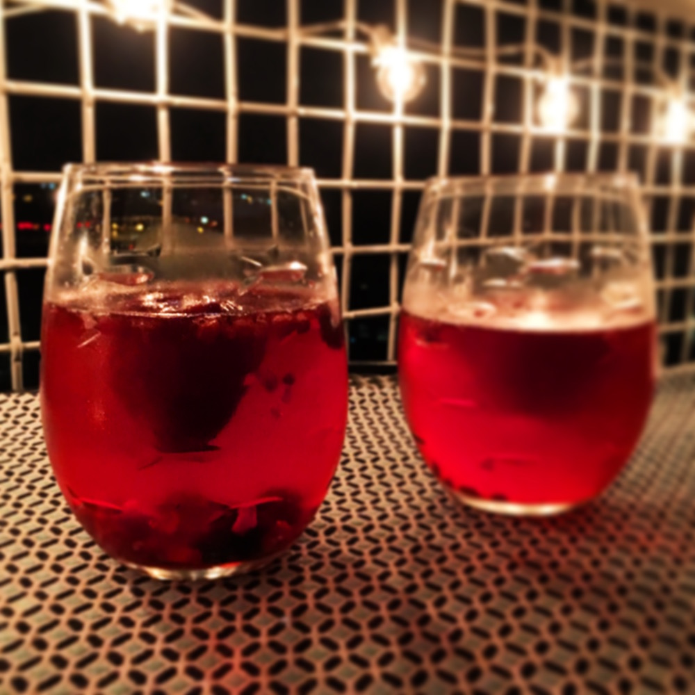 The fruits of our labor under our porch lights. Note the full strawberry floating in the (now) berry red Cava. Delicious!