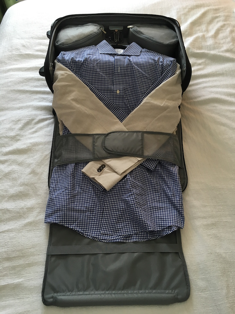 The top opens into a full size garment bag that, depending on your size, can do you for up to two suits (or dresses). I've a blazer, button down, and two pairs of pants in here now. Use the corner pockets to pack your under garments.
