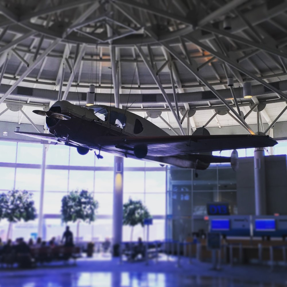 The International Terminal (Terminal D) in Charlotte (CLT) greets arriving passengers with a historic plane suspended in its rotunda.
