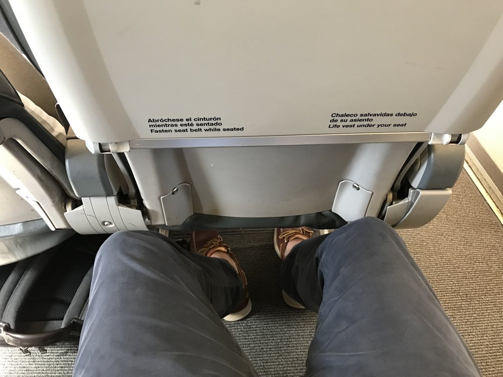 Legroom is the same in business class as in economy (so not great), but getting to store things in the empty middle seat means you've nothing under the seat in front of you.