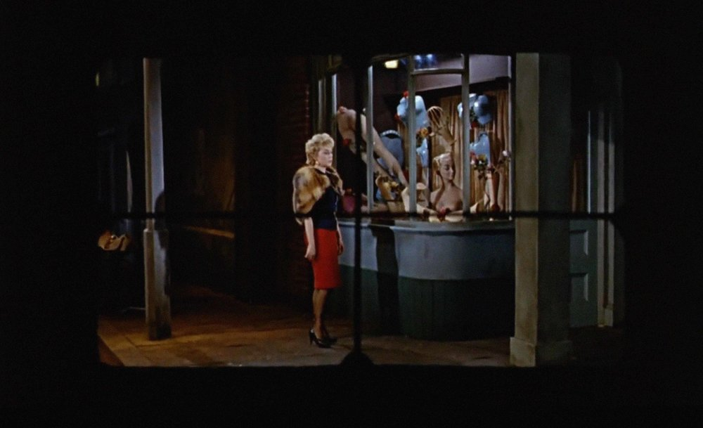 Powell foreshadows the death of the prostitute by placing her beside a window of of a severed mannequin.