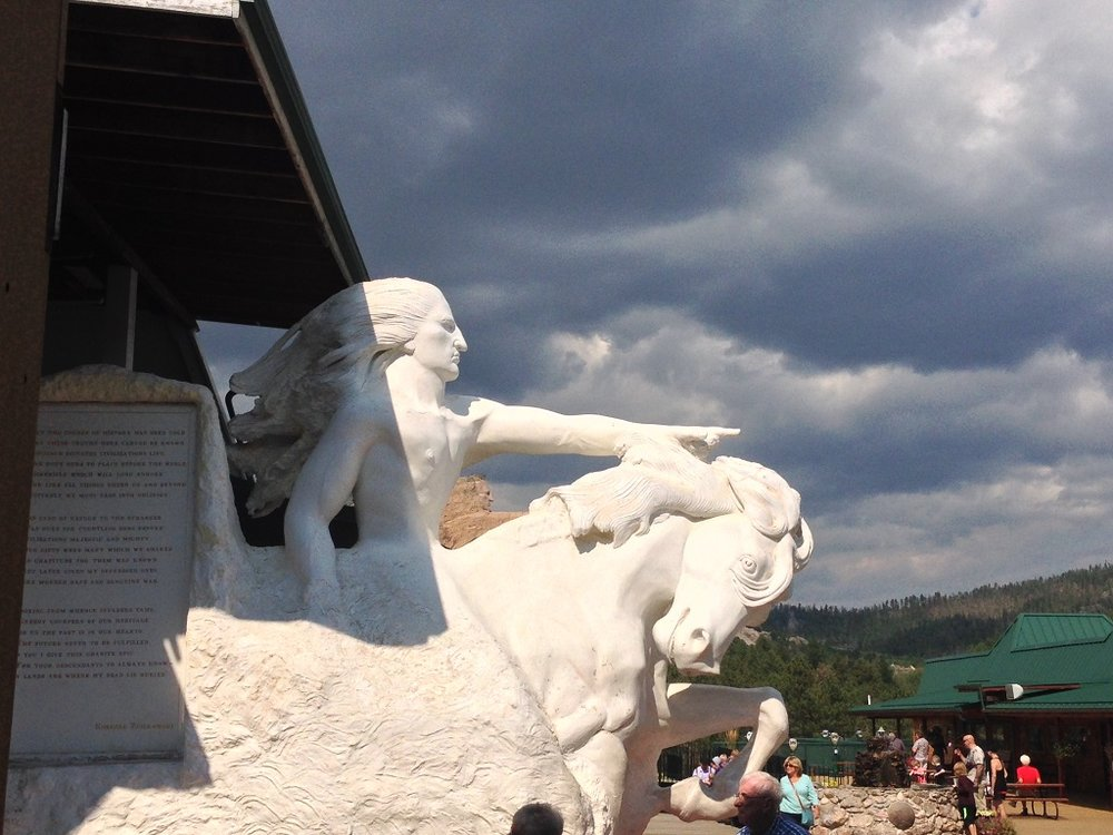 Crazy Horse model with actual monument in background.