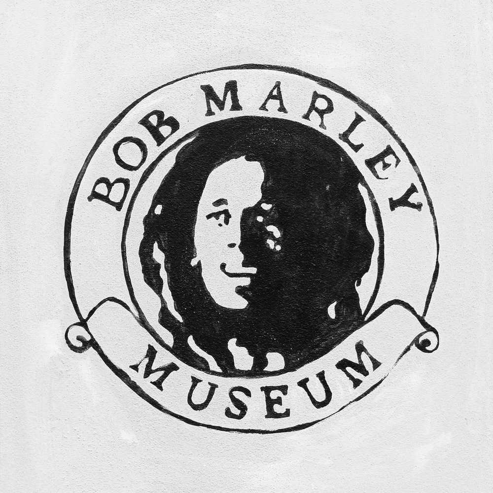 bob marley museum dayglow before the tour begins you are encouraged to wander the grounds there are large vivid mural styled paintings and photographs covering the walls