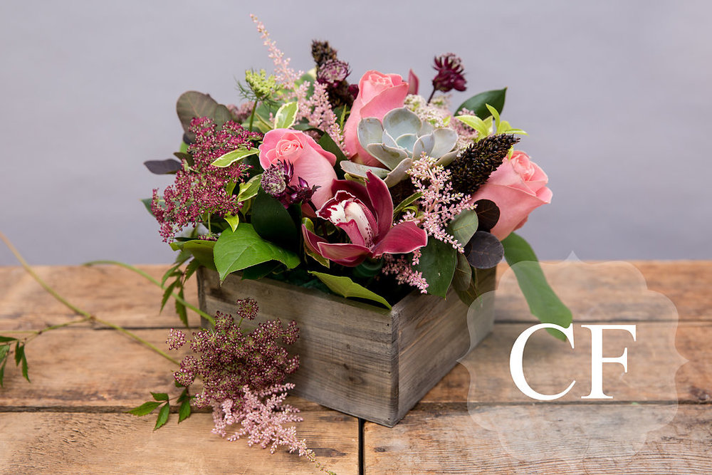 Our popular wood box arrangement comes in your choice of colors. Here we have chosen plums and light pinks, a modern take on fall. Shop the wood box arrangement  here.