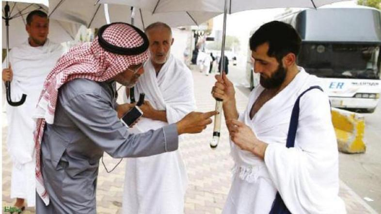 Kamal Badawi, a Saudi engineer from Makkah, explains the features of a smart umbrella to a pilgrims. (Source:  Al Arabiya)