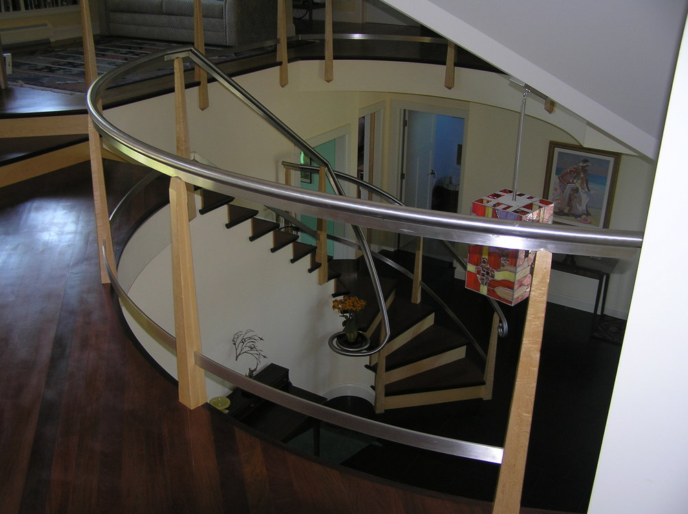 radius stair and balcony with Brazilian cherry treads, curly maple risers and newel posts.