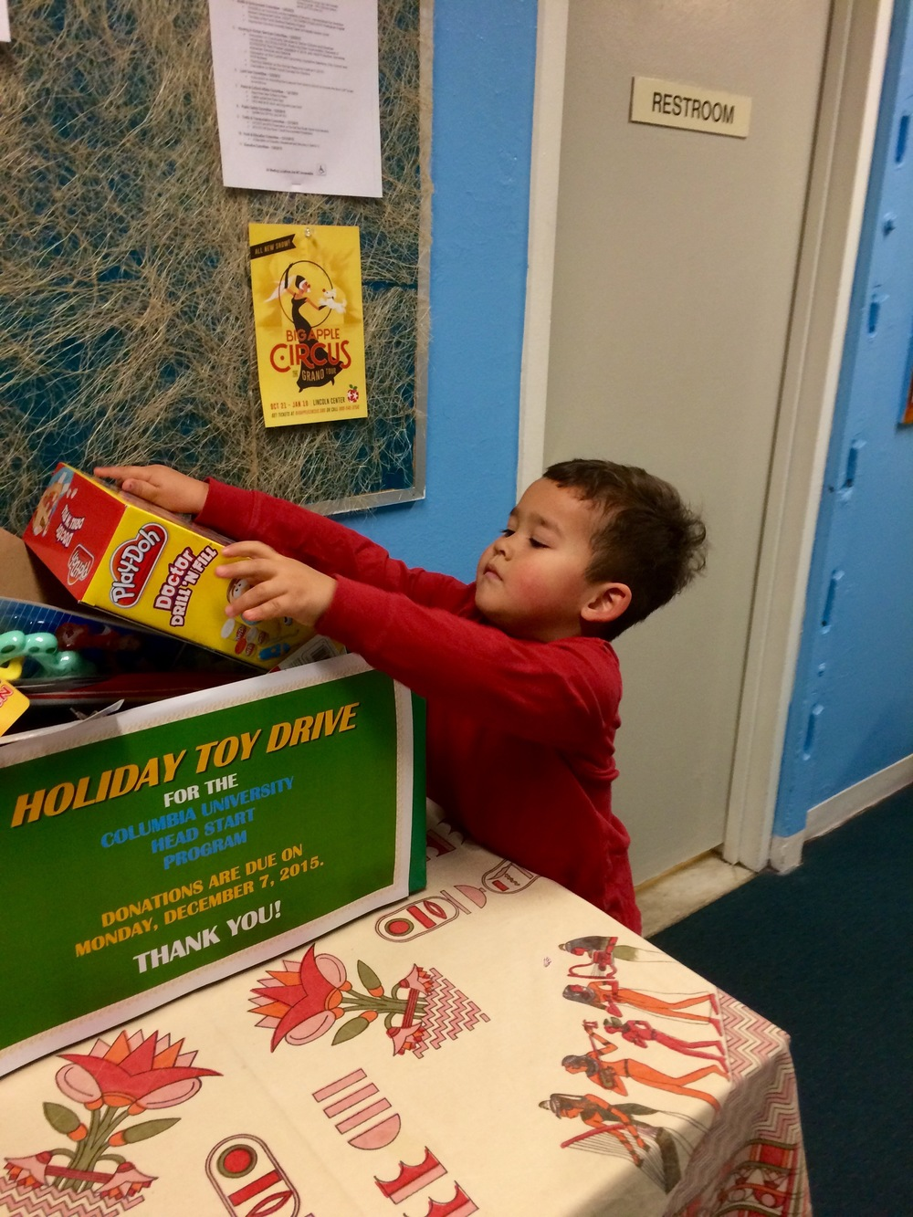 Donating a toy to Milo's school Holiday Toy Drive for the local Head Start program.