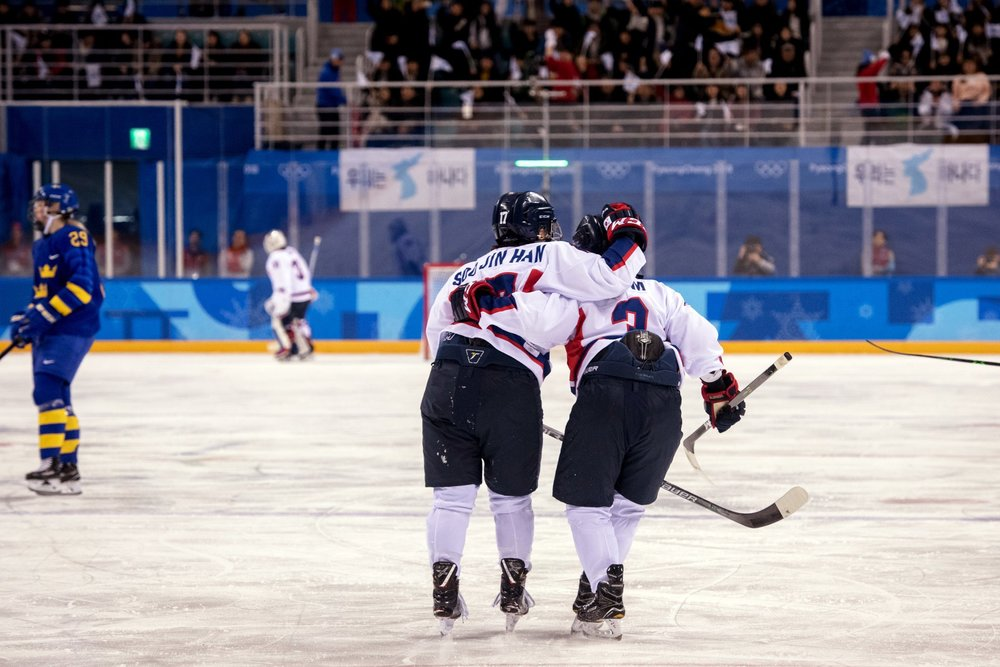 <Two members of the joint-Korean hockey team celebrate together>  Photo from:  https://www.nytimes.com/2018/02/20/sports/unified-Korean-hockey-team.html