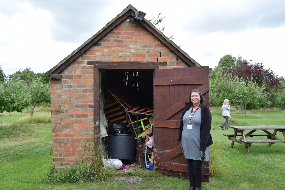 Emily at the onion shed full of rubbish.JPG