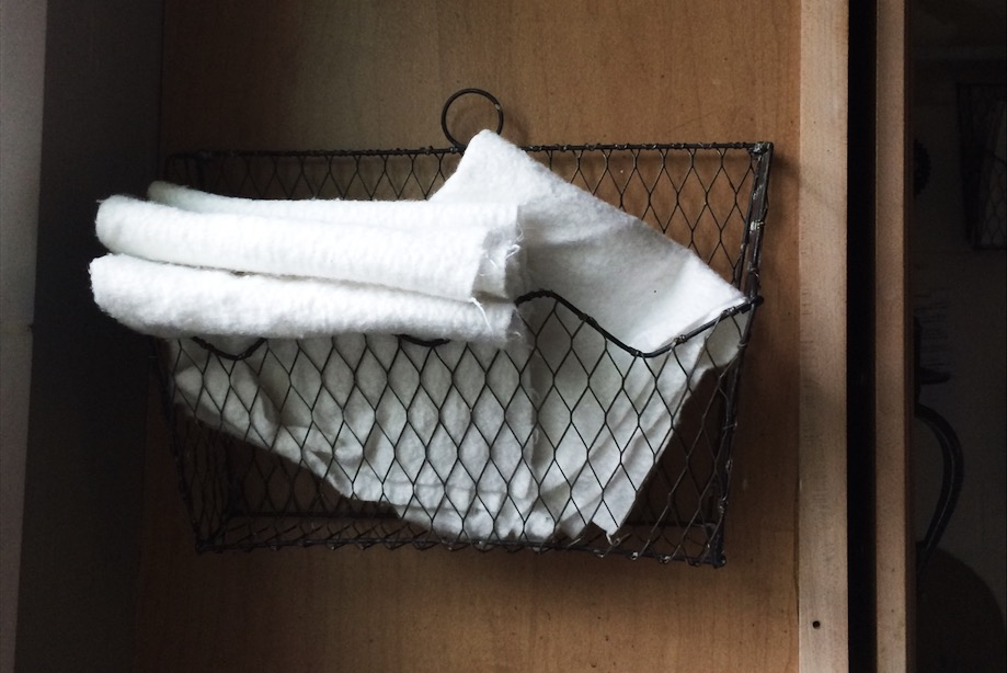 A small basket on the cabinet by the sink holds gently folded towels for reuse.