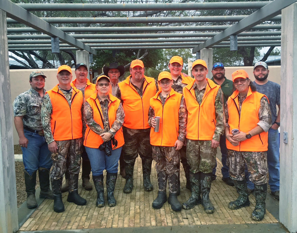 2017 Heritage Hunt Participants - (back row) Hixon ranch guides Landon Gulick, Brock Minton (TX Parks & Wildlife), Eddie Price, Mike Hehman (ranch manager), and Blake Martin join hunter education instructors and students/parents selected for the IHEA-USA Heritage Hunt(front row/orange) Mike McDonald (WA), Dorothy Pezzi (FL), Mitchell and Blake Anderson (ID), and Michael and Paul Fraley (MI), John Pezzi (FL) (not pictured: Damion and Jimmy Byers, NC).