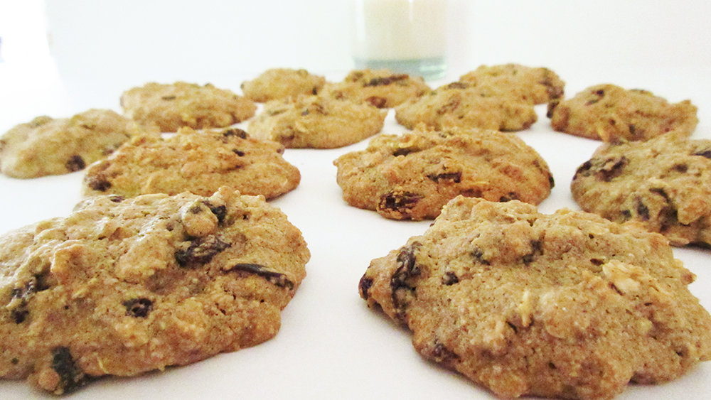 oatmeal raisin cookies cookies stacked with glass beside it.jpg