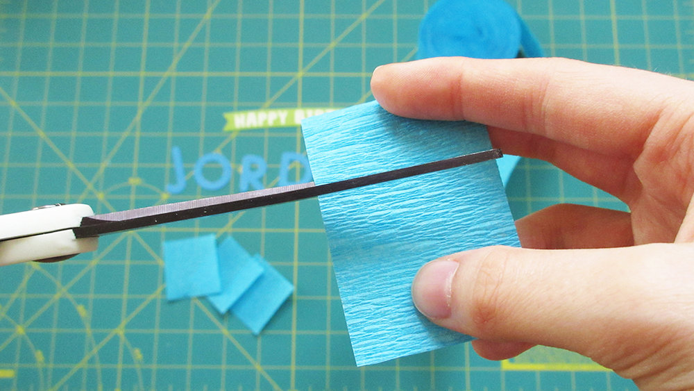 Cutting blue crepe paper streamer into squares for DIY Streamer Name Cake Topper