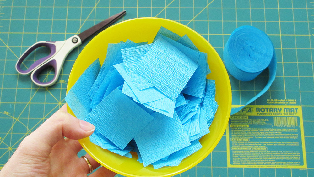 Holding yellow bowl filled with cut out blue streamer squares for DIY Streamer Name Template