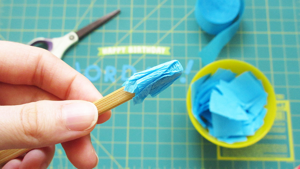 Showing the finished pinched blue crepe paper square on the chopstick