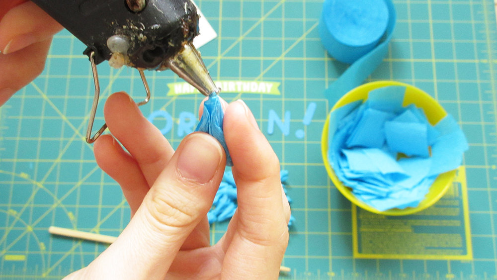 Applying hot glue to the folded blue crepe paper piece