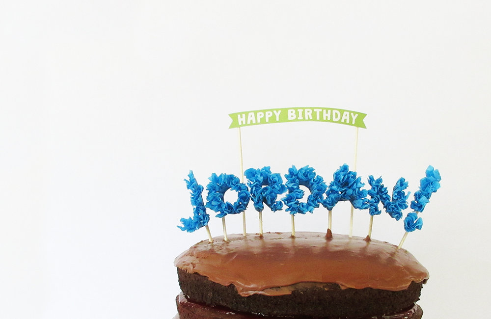 DIY Streamer Name Cake Topper placed in chocolate birthday cake