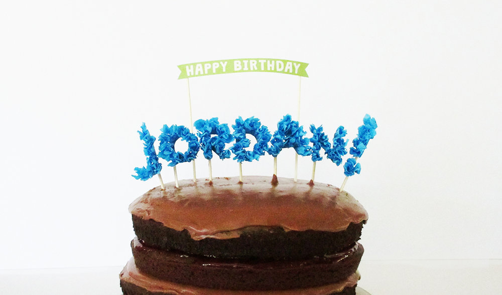 DIY Streamer Name Cake Topper And Happy Birthday Banner On Top Of Chocolate