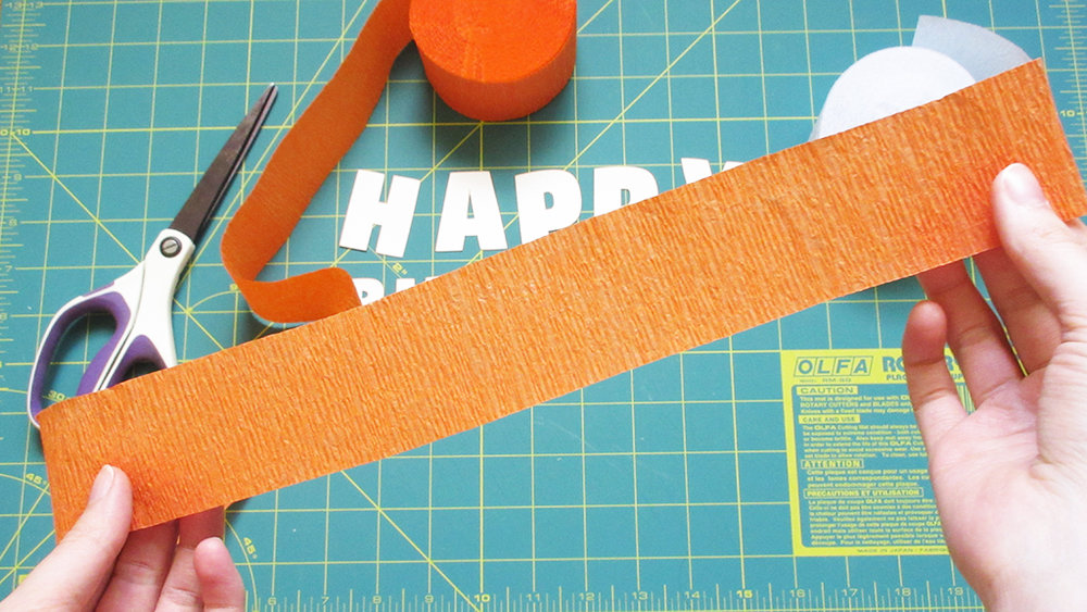 Holding about a foot of orange crepe paper party streamer