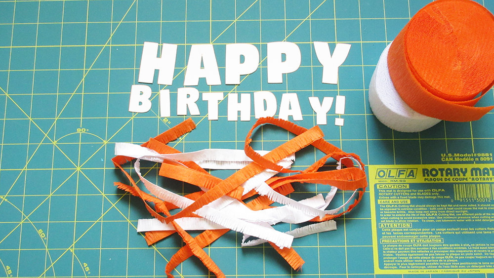 A pile of orange and white crepe paper party streamers all cut and ready to make cake topper