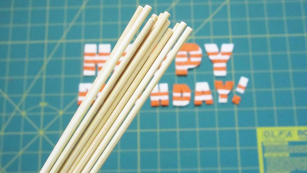Holding skewers about to be glued to the back of DIY Pinata Letters Cake Topper letters