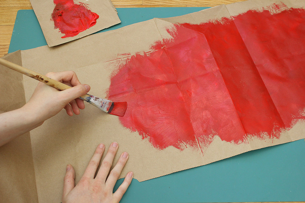 Painting brown paper bag red for berries of the DIY Christmas Holly Leaf Decoration