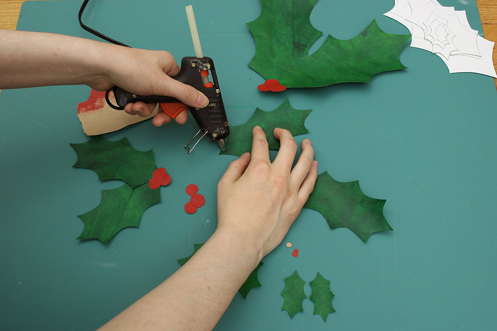 Adding hot glue to Holly Leaf Christmas decoration