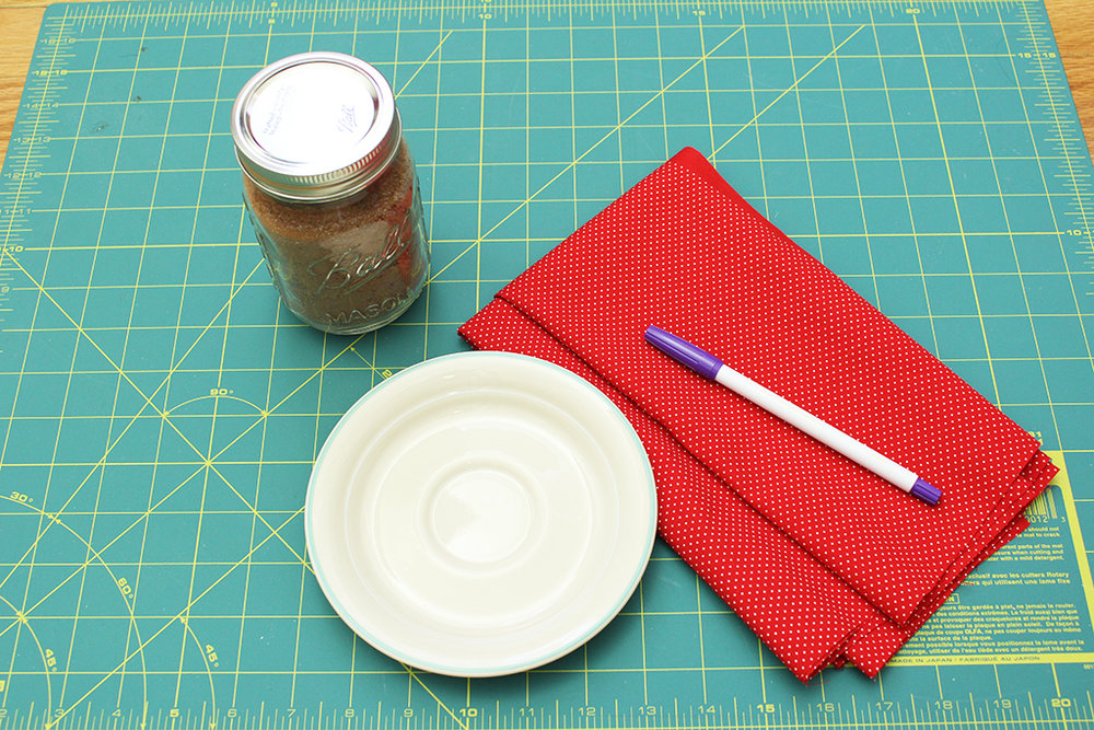 Jar of cocoa, a small plate, polka-dot fabric, and a fabric pen on fabric cutting mat
