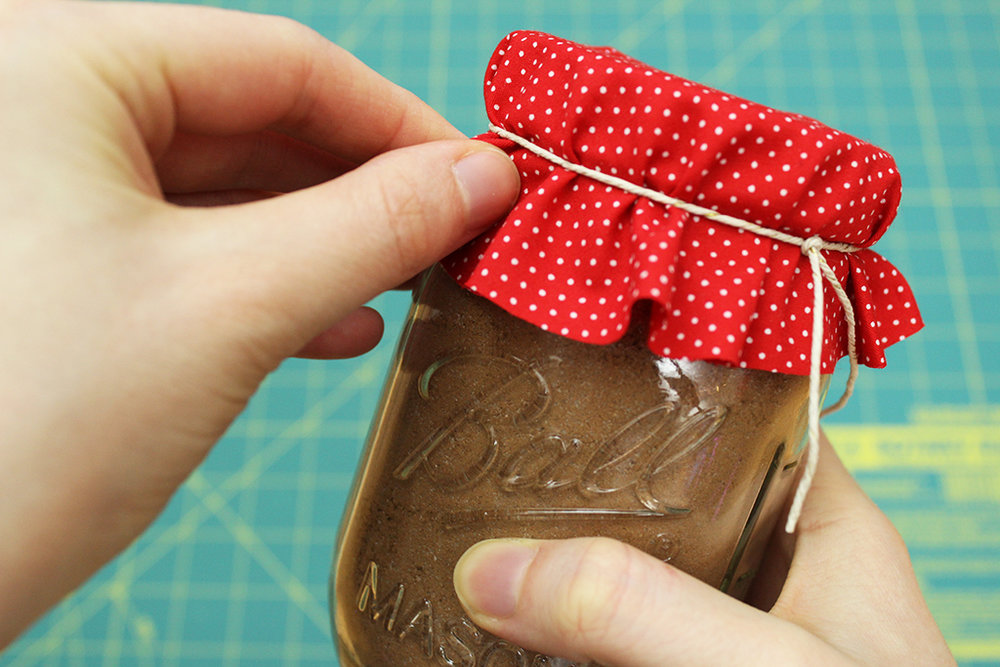 Adjusting fabric bunching on Vegan Candy Cane Cocoa Mix jar