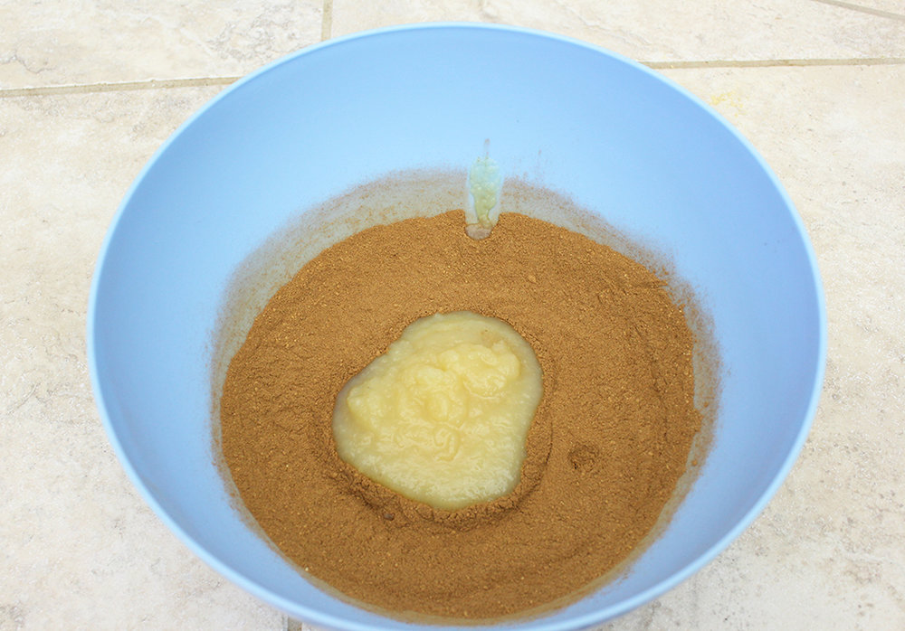 Cinnamon, ginger and applesauce in a bowl to make Gingerbread Cookie Garland dough