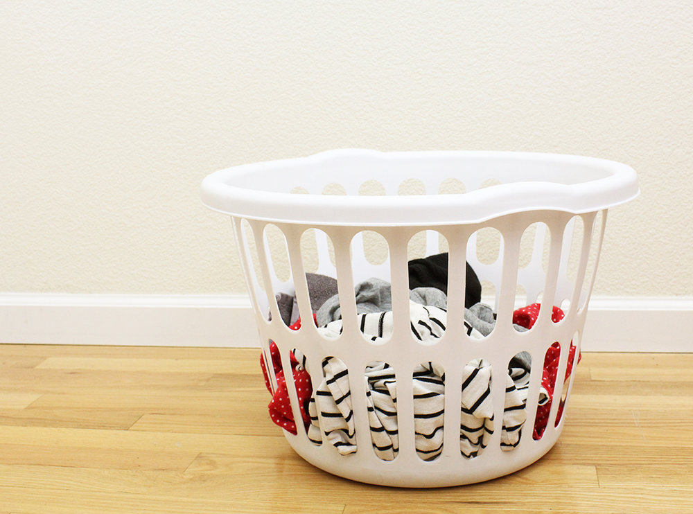 White laundry basket sitting on floor with clothes in it