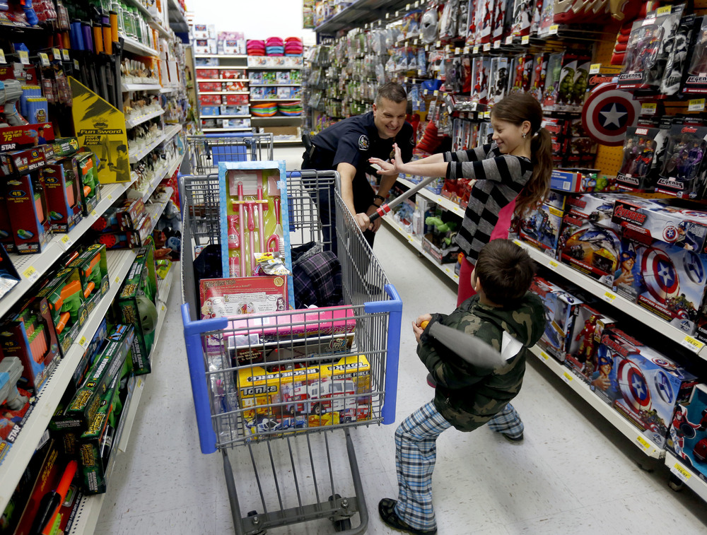 Audrea Martinez, right, 9 of Richland, tries to break up a play toy fight between her brother Roman Canon, 5, and Richland Police Department Officer Eric Edwards Saturday  December 12, 2015 during the Shop with a Cop event at the Richland Wal-Mart.  Multiple local law enforcement agencies helped local kids holiday shop with $100 gift cards during the second of three local events.