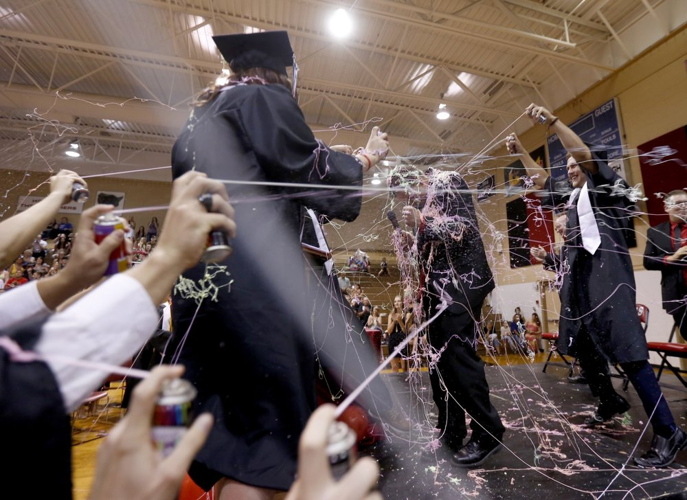 Graduates spray principal Bryan Long with silly string Friday during River View High School's Graduation at the school in Finley.