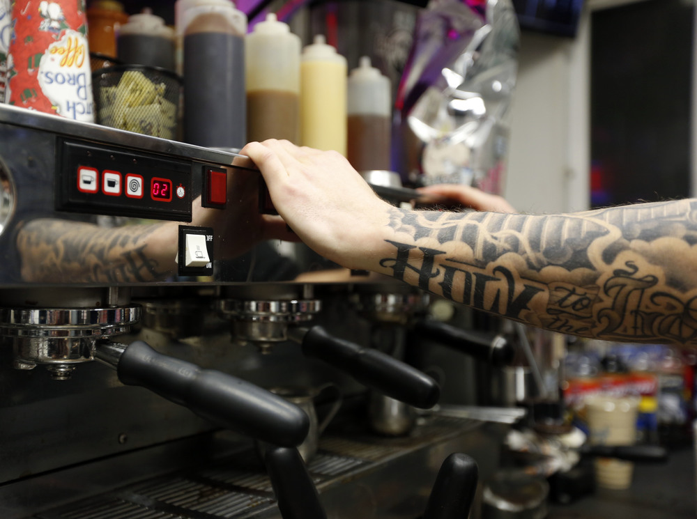Zade Hakki cleans the espresso machine while working at 12 a.m. on the graveyard shift at Dutch Bros. Coffee on Clearwater Avenue in Kennewick. For Hakki the job isn't about making coffee but the conversations with customers.