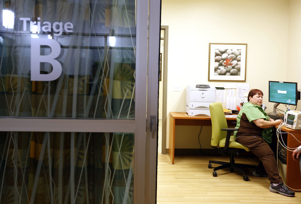 Patsy Haeg, an overnight charge nurse in the emergency department at Trios Southridge Hospital in Kennewick, talks with a patient during the 1 a.m. hour.