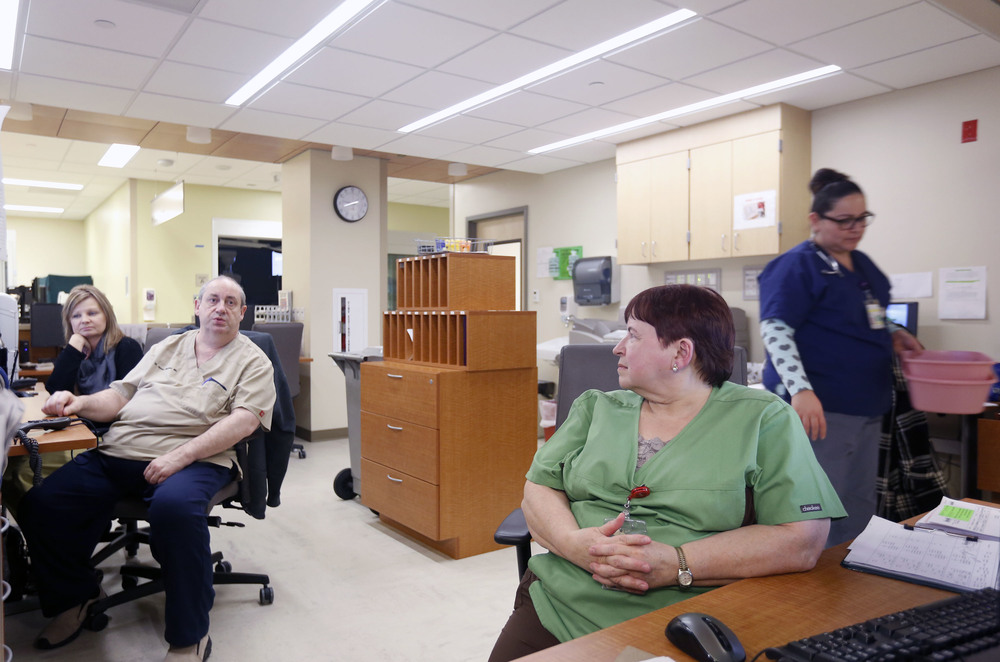 Patsy Haeg, an overnight charge nurse in the emergency department at Trios Southridge Hospital in Kennewick, talks with coworkers during the 1 a.m. hour