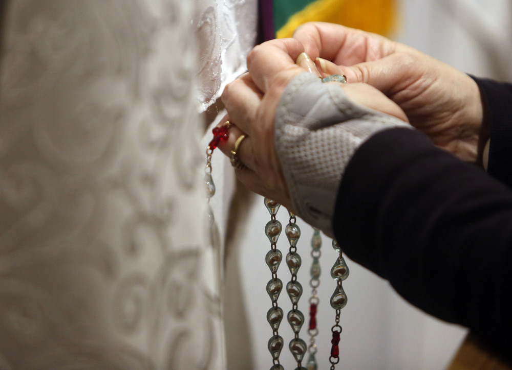 Carol LeCompte, 66, of Kennewick, holds rosary beads and prays in the perpetual adoration chapel at St. Joseph Catholic Church in Kennewick during the 2 a.m. hour.