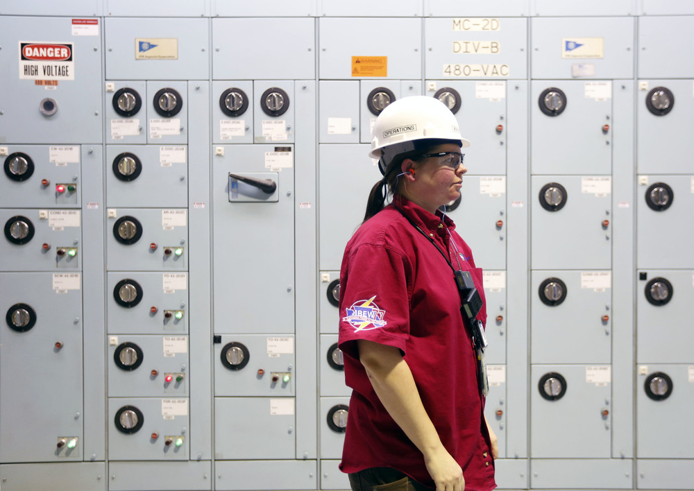Angela Deahl, an equipment operator, stands in front of a wall of equipment during her overnight shift at the Columbia Generating Station near Richland. Deahl, who started her career in the Navy, is one of two women on a team of 39 equipment operators at the plant.