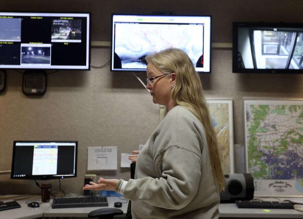 Various weather maps and computer screens of satellite and radar images frame meterologist Mary Wister as she talks to a co-worker during an overnight shift at the National Weather Service in Pendleton. With two decades in the field, Wister has seen significant technological advancements that change how she does her job