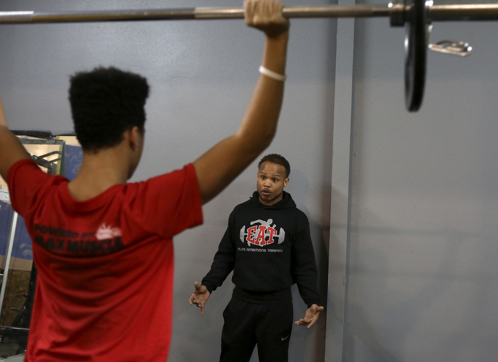 Steven Whitehead talks to Jordan Gray, a Kennewick High School junior, during a early morning training session with high school athletes at Elite Ambitions Training in Kennewick. Whitehead, founder and owner of E.A.T., came to Kenenwick in 2011 to play for the Tri-Cities Fever but surprised himself by making a home here.